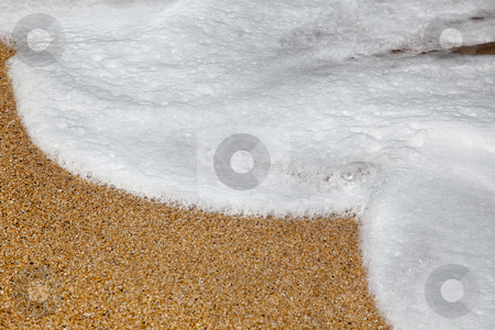 Foam on beach stock photo, Background image of foam and waves on a sandy beach by Anneke