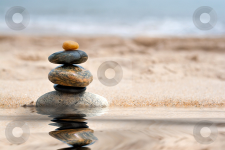 Stacked Zen Rocks Reflection stock photo, A pile of round smooth zen like stones stacked in the sand at the beach with a mirror reflection from a pool of water. by Todd Arena