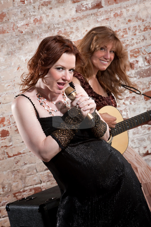 Female musicians stock photo, Woman sings along with guitar in front of a brick background by Scott Griessel