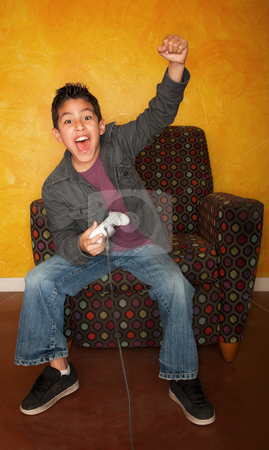 Hispanic Boy Playing Video Game stock photo, Handsome young Hispanic boy playing a video game by Scott Griessel