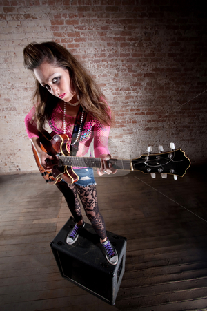 Punk Rock Girl stock photo, Punk rocker girl alone with her guitar by Scott Griessel