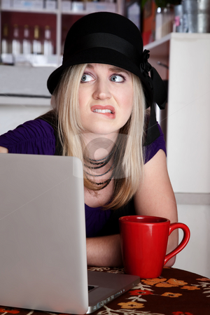 Worried young wamn in cafe with laptop computer stock photo, Worried blond girl with laptop and mug at a cafe by Scott Griessel
