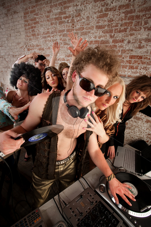 1970s Disco Music Party stock photo, Cool DJ with vest and female admirers by Scott Griessel