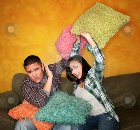 Pillow Fight stock photo, Hispanic couple on couch play fighting with pillows by Scott Griessel