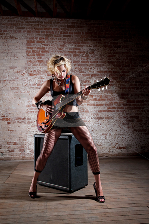 Female punk rocker stock photo, Female punk rock guitarist alone in a warehouse with a large speaker by Scott Griessel