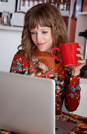Working stock photo, Pretty young woman working on a laptop and drinking by Scott Griessel
