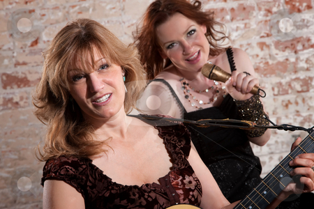 Female musicians stock photo, Woman plays a guitar with singer in front of a brick background by Scott Griessel