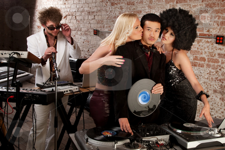 1970s Disco Music Party stock photo, Enviable Asian DJ with admiring female friends by Scott Griessel