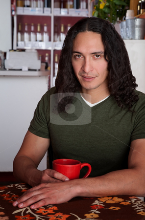 Handsome stock photo, Handsome Latino male sitting alone in a cafe by Scott Griessel