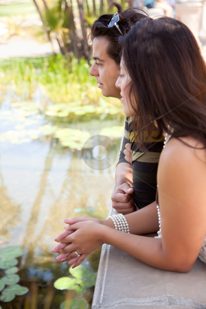 Attractive Hispanic Couple Overlook Pond stock photo, Attractive Hispanic Couple Overlook Pond Together Outdoors. by Andy Dean
