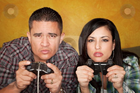 Hispanic Couple Playing Video game stock photo, Attractive Hispanic Couple Playing a Video Game with Handheld Controllers by Scott Griessel