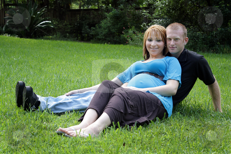 Couple Outdoors stock photo, A husband and wife sitting in the grass.  The wife is approximately 26 weeks pregnant. by Carl Stewart