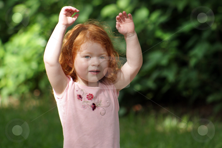 Cute Redhead Girl on a Playground (15) stock photo, An adorable two-year-old redhead girl on a playground, raises her hands in the air. by Carl Stewart
