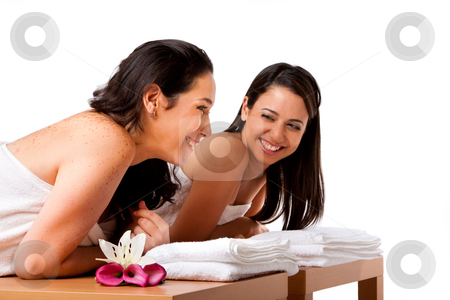 Women having fun at spa stock photo, Two beautiful women friends laying on wooden tables with towels waiting for their massage in the spa, smiling laughing talking and having fun, isolated. by Paul Hakimata