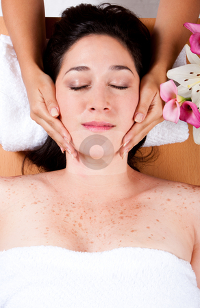 Luxury facial massage stock photo, Skincare consultant applying fasial massage on beautiful woman at a spa salon. by Paul Hakimata