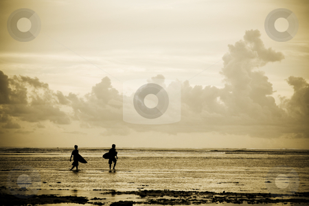 Surfers on the beach stock photo, A silhouette shot of a couple of surfers on the beach during sunset by Suprijono Suharjoto