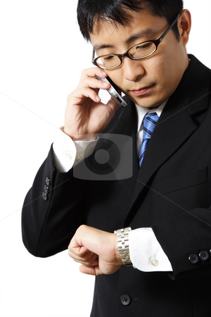 Businessman stock photo, Businessman talking on the phone while looking at his watch by Suprijono Suharjoto