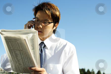 Businessman stock photo, Businessman reading financial newspaper while making a phone call by Suprijono Suharjoto