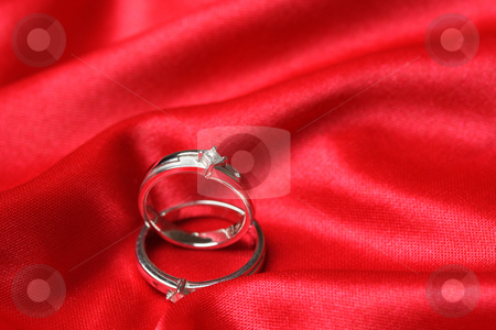 Wedding rings stock photo, A pair of wedding rings on a red cloth by Suprijono Suharjoto
