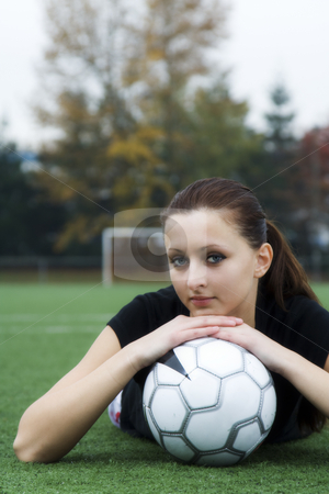 Soccer girl stock photo, A beautiful soccer player resting on a soccer ball by Suprijono Suharjoto