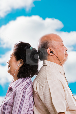 Senior asian couple listening to music stock photo, A happy senior asian couple listening to music outdoor by Suprijono Suharjoto