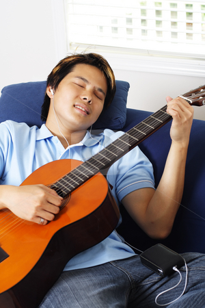 Guitar player stock photo, Young man relaxing at home by playing guitar by Suprijono Suharjoto