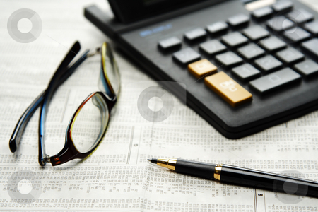 Personal finance stock photo, Calculator and glasses and pen on top of financial newspaper by Suprijono Suharjoto