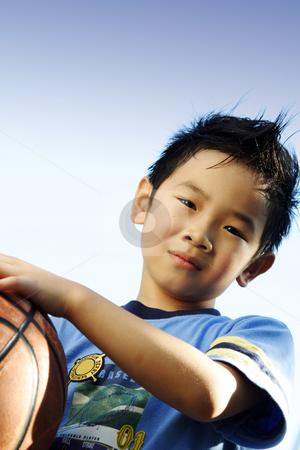 Sporty boy stock photo, A boy playing basketball outside by Suprijono Suharjoto
