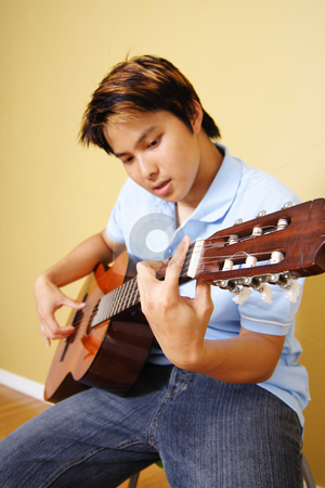 Guitar player stock photo, A young man playing guitar by Suprijono Suharjoto