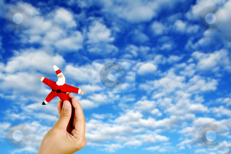 Santa Claus stock photo, Holding up Santa figure against blue sky and layers of clouds by Suprijono Suharjoto