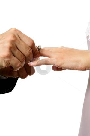 Wedding stock photo, The groom inserting a diamond wedding ring into the bride's finger by Suprijono Suharjoto