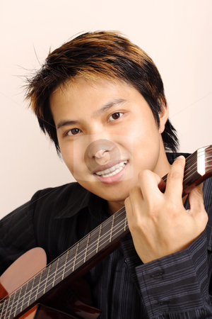Guitar player stock photo, A handsome man holding a guitar by Suprijono Suharjoto