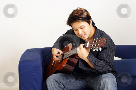 Guitar player stock photo, A handsome man playing a guitar by Suprijono Suharjoto