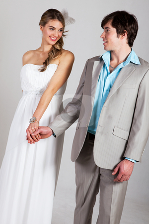 Smiling Young Couple Holding Hands stock photo, Attractive young and well dressed couple hold hands and smile at one another. Vertical shot. by Angela Hawkey