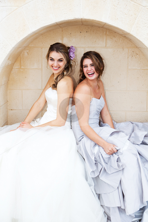 Young Women in Gowns and Sitting in an Alcove stock photo, Two attractive young women wearing formal dresses are smiling and sitting back to back in an alcove. Vertical shot. by Angela Hawkey