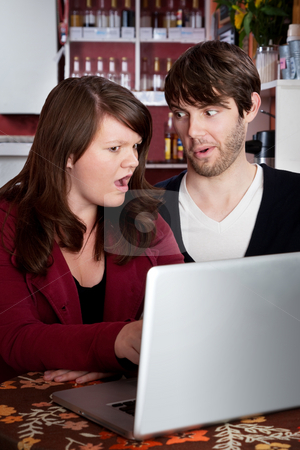 Woman and man staring in disbelief at a computer laptop stock photo, Woman and man staring in disbelief at a laptop by Scott Griessel