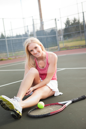 Tennis player stock photo, A beautiful caucasian tennis player stretching on the tennis court by Suprijono Suharjoto