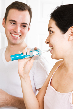 Couple brushing teeth in the bathroom stock photo, A beautiful interracial couple in the bathroom brushing teeth by Suprijono Suharjoto