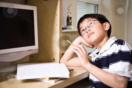 Studying kid stock photo, A shot of an asian kid studying at home by Suprijono Suharjoto
