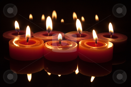 Red candles with flames on a dark background stock photo, Glowing flames from candles with reflections top and bottom by Stephen Clarke