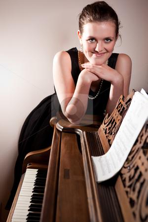Beautiful teenager playing piano stock photo, A portrait of a beautiful teenager playing piano by Suprijono Suharjoto