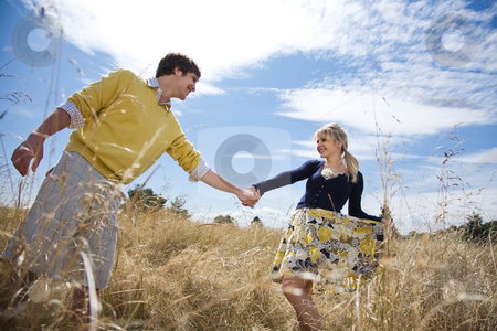 Young caucasian couple in love stock photo, A young caucasian couple in love having fun on a grassy field by Suprijono Suharjoto