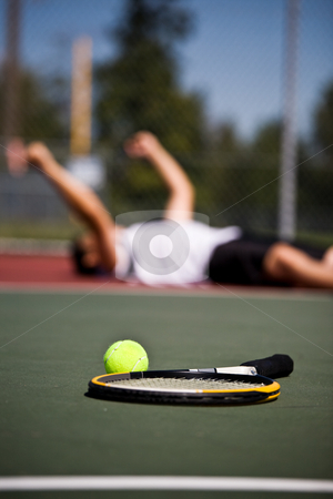 Happy tennis player after winning stock photo, A happy young tennis player lying down on the court after winning by Suprijono Suharjoto