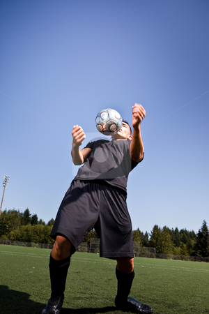Hispanic soccer or football player with soccer ball stock photo, A shot of a hispanic soccer or football player controlling the ball with his chest by Suprijono Suharjoto
