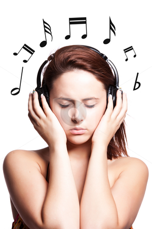 Beautiful woman listening music stock photo, An isolated shot of a beautiful caucasian woman listening to the music with headphones by Suprijono Suharjoto