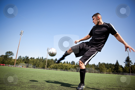 Hispanic soccer or football player kicking a ball stock photo, A shot of a hispanic soccer or football player kicking a ball by Suprijono Suharjoto