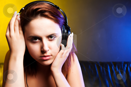 Beautiful woman listening to music stock photo, A shot of a beautiful caucasian woman sitting on the sofa listening music with headphones by Suprijono Suharjoto