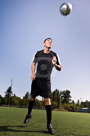 Hispanic soccer or football player heading a ball stock photo, A shot of a hispanic soccer or football player heading a ball by Suprijono Suharjoto
