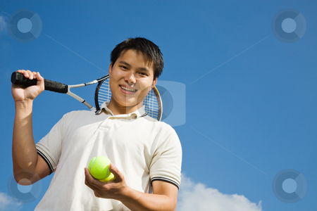 Asian male playing tennis stock photo, A happy sporty asian male playing tennis by Suprijono Suharjoto