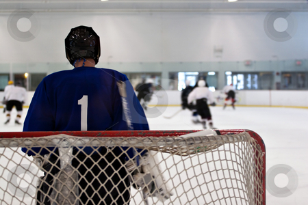Hockey Goalie stock photo, A hockey goalie awaiting the return of the puck so he can resume his defensive role.  Shallow depth of field. by Todd Arena